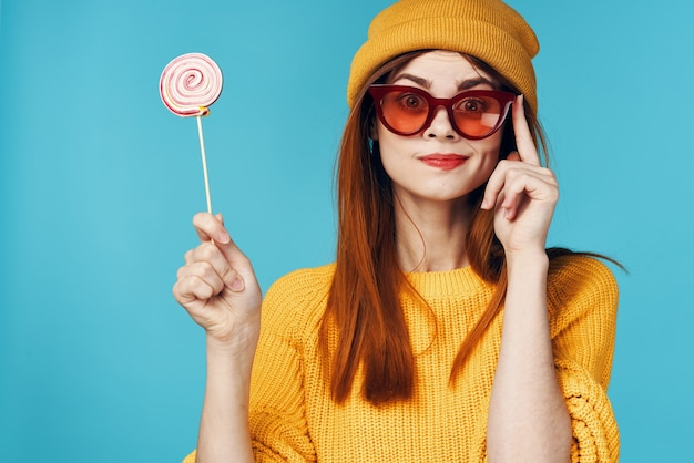 Mulher alegre e glamorosa com pirulito de óculos na mão, chapéu amarelo e fundo azul