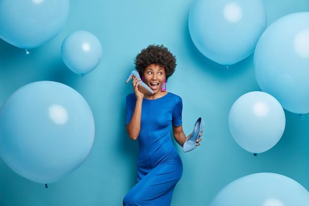 Mulher alegre e inspirada dança despreocupada com prazer, tem clima de festa, gosta de música, vestida de vestido de cocktail azul, segura os sapatos nas mãos, passa o tempo livre em comemoração, rodeada de balões