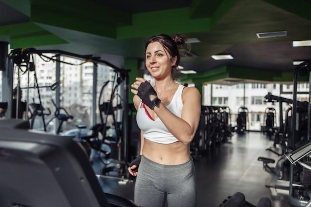 Mulher alegre e magra em roupas esportivas em uma esteira na academia