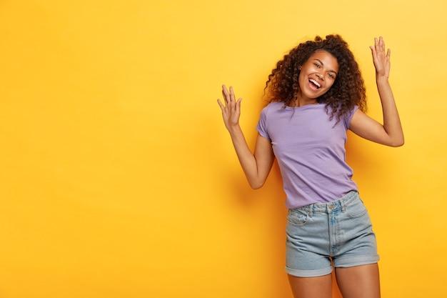 Mulher alegre e otimista de cabelos cacheados levanta os braços, fica radiante, dança ativamente, se diverte na festa, usa camiseta roxa casual e shorts jeans
