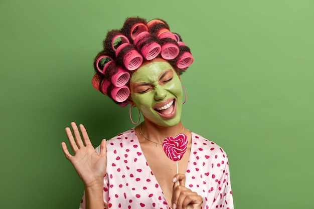 Mulher alegre e positiva levanta a palma da mão, canta a música favorita, usa pirulito no bastão como microfone, calafrios em casa durante procedimentos de beleza usa máscara hidratante verde no rosto, rolos de cabelo. conceito de beleza