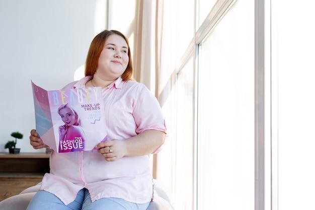Mulher alegre e positiva olhando pela janela enquanto está sentada com uma revista nas mãos