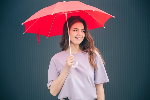 Mulher alegre e positiva sob o guarda-chuva vermelho e olhar certo
