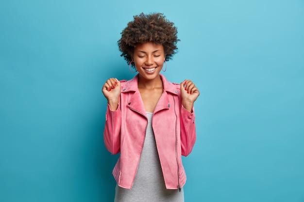 Mulher alegre e satisfeita tem cabelos afro, fecha os olhos e aperta os punhos, aguarda o momento especial, sorri agradavelmente, estar bem vestida