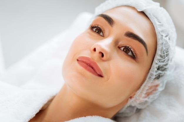 Mulher alegre e simpática deitada em uma cama médica enquanto espera por um procedimento de beleza