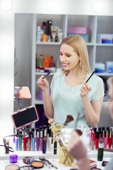 Mulher alegre e simpática em frente à câmera enquanto grava um vídeo para seu blog de beleza