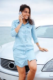 Mulher alegre e sorridente em pé perto do carro e usando o celular à beira-mar