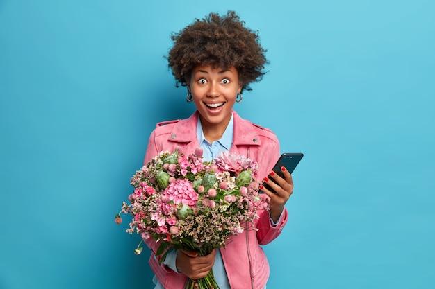 Mulher alegre e surpresa segurando um celular moderno aceita parabéns pelas poses de aniversário com um buquê de flores festivo isolado na parede azul