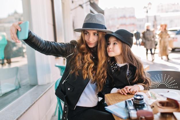 Mulher alegre elegante de cabelos castanhos no chapéu de feltro, fazendo selfie com filha encantadora, esperando o café no café.