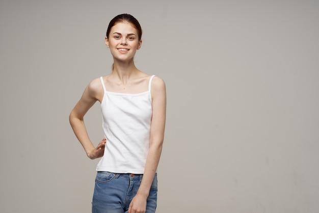 Mulher alegre em camiseta branca aquecimento ombros saúde