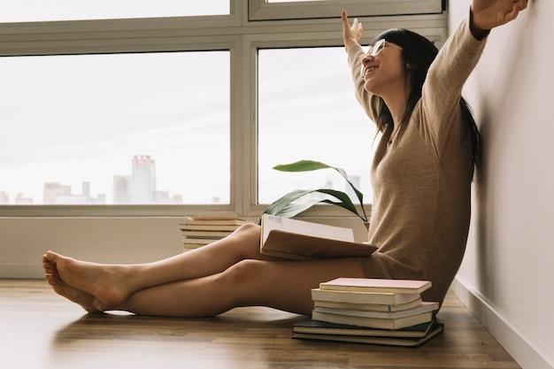 Mulher alegre em copos lendo no chão