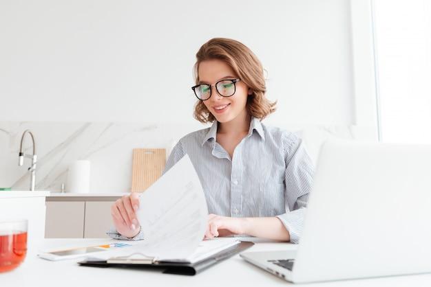 Mulher alegre em copos lendo novo contrato enquanto trabalhava na cozinha