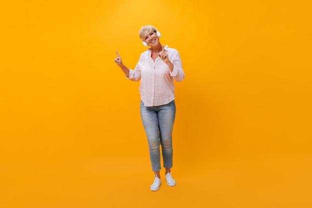 Mulher alegre em fones de ouvido dançando em fundo laranja