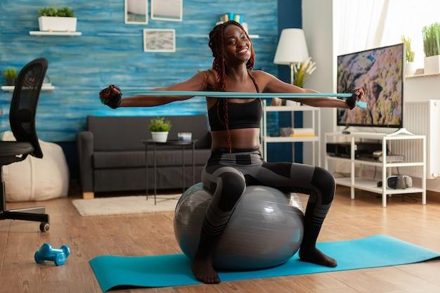 Mulher alegre em forma atlética, exercitando os músculos das costas com elástico, sentada na bola de estabilidade na sala de estar de casa para um estilo de vida saudável