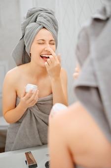 Mulher alegre em frente ao espelho do banheiro esfrega o rosto com um creme para a pele. conceito de juventude e cosmetologia.