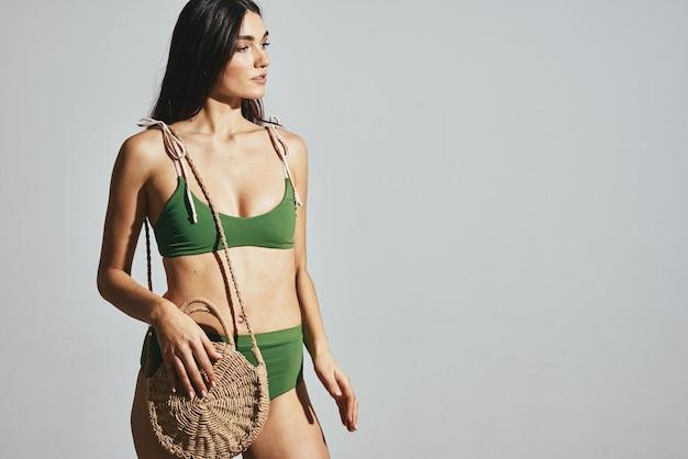 Mulher alegre em maiô verde bolsa de praia na moda para viagens