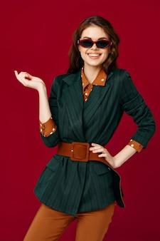 Mulher alegre em óculos de sol de terno sorriso cortada vista vermelha