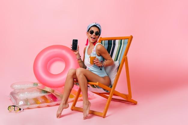 Mulher alegre em óculos de sol sentada na espreguiçadeira com um gadget