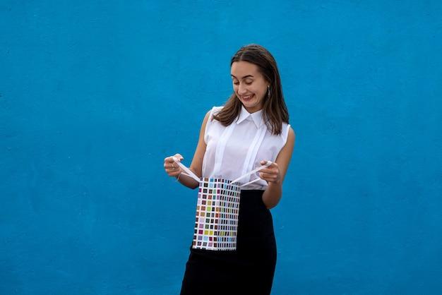 Mulher alegre em pano de estilo de negócios segura sacos de pechinchas de off-sales sobre fundo de cor azul. estilo de vida de compras ou compras online