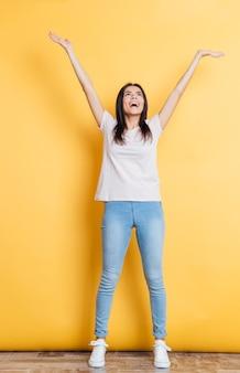Mulher alegre em pé com as mãos levantadas na parede amarela