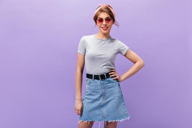 Mulher alegre em poses de óculos rosa em fundo isolado. garota maravilhosa com bandana em camiseta cinza e saia jeans sorrindo.