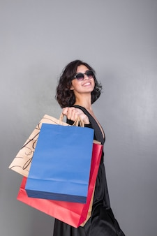 Mulher alegre em preto com caixas de presente