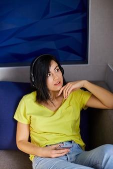 Mulher alegre em roupas casuais com fones de ouvido e smartphone, ouvindo podcast no sofá em casa.