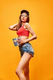 Mulher alegre em roupas casuais em pé com pipoca em fundo laranja