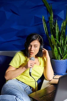 Mulher alegre em roupas casuais gravando um podcast, falando em um microfone com fones de ouvido e laptop, notebook