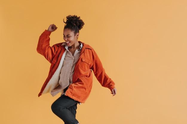 Mulher alegre em um blusão dançando na parede amarela