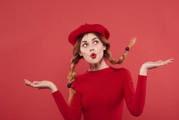 Mulher alegre em um estúdio de emoção de cosméticos camisola vermelha posando. foto de alta qualidade