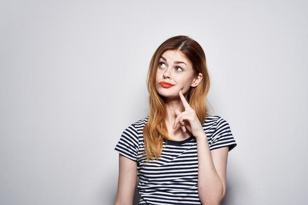 Mulher alegre em um gesto de camiseta listrada com seu estúdio de modelos de mãos