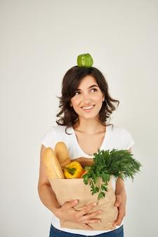 Mulher alegre em um pacote de camiseta branca com verduras de legumes