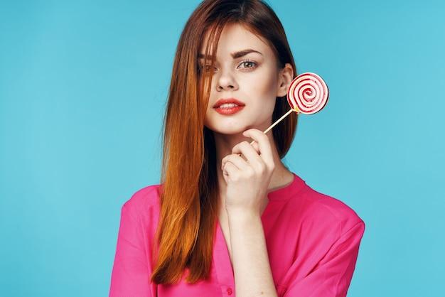 Mulher alegre em um pirulito de camisa rosa no luxo de emoções de mãos
