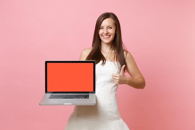 Mulher alegre em um vestido branco aparecendo o polegar, segurando o computador laptop com a tela preta vazia