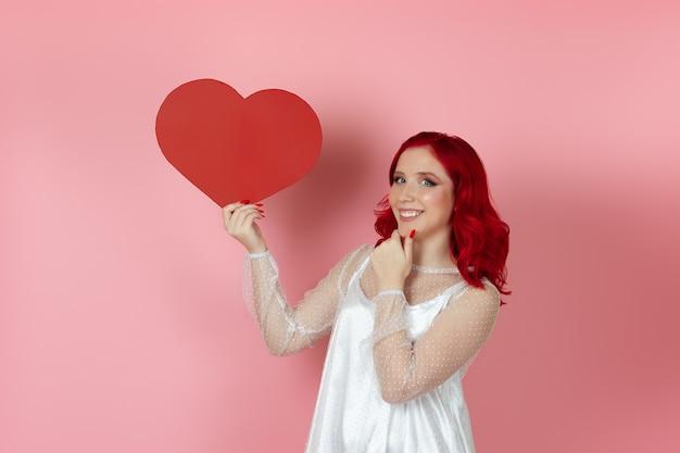 Mulher alegre em um vestido branco e cabelo ruivo segura um grande coração de papel vermelho e esfrega o queixo