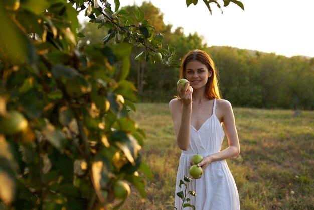 Mulher alegre em um vestido branco em maçãs naturais