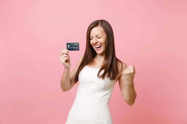 Mulher alegre em um vestido branco segurando um cartão de crédito e fazendo um gesto de vencedor