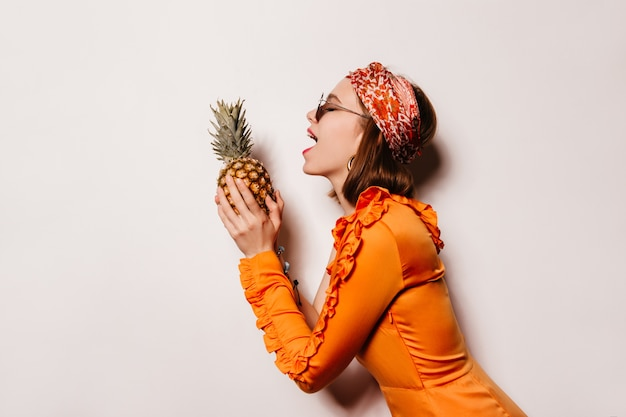 Mulher alegre em um vestido de cetim laranja e óculos quer morder o abacaxi.