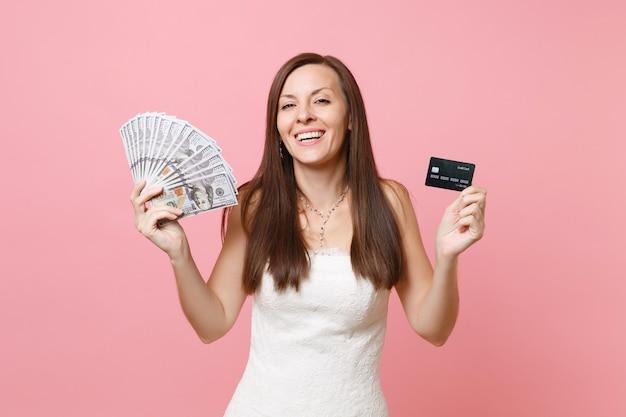 Mulher alegre em um vestido de renda branca segurando um pacote de muitos dólares, dinheiro em espécie e cartão de crédito