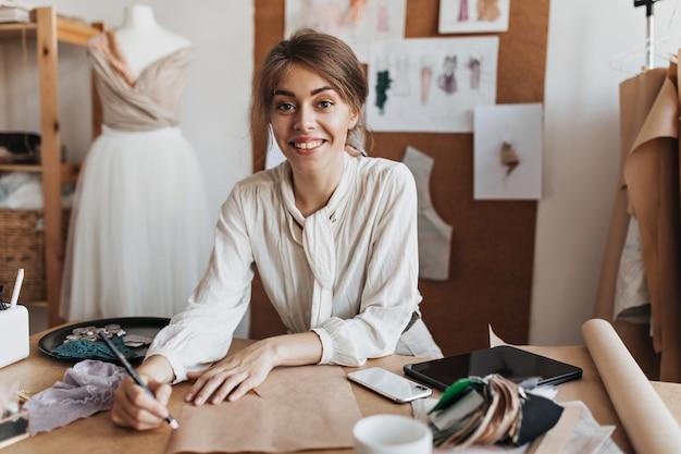 Mulher alegre em uma blusa elegante desenhando um esboço
