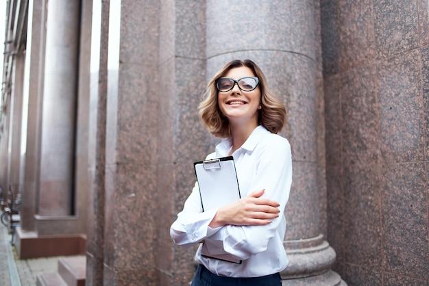 Mulher alegre em uma camisa branca gerente documenta ao ar livre