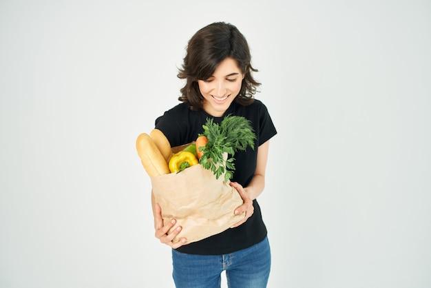 Mulher alegre em uma camiseta preta sacola de comida vegetais alimentos saudáveis closeup