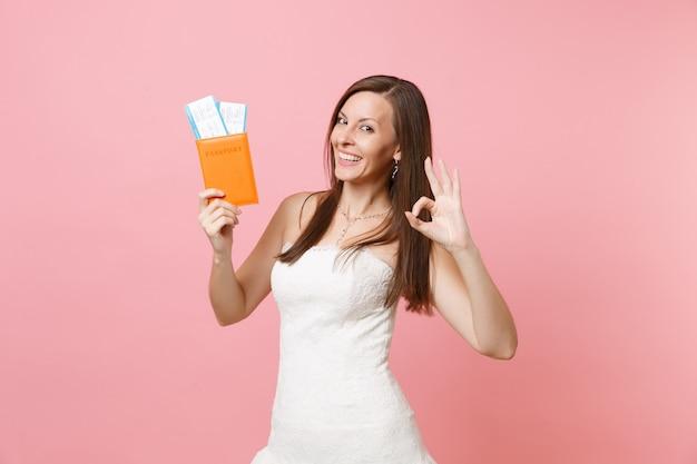 Mulher alegre em vestido branco mostrando sinal de ok, passaporte e passagem de embarque, viagem ao exterior