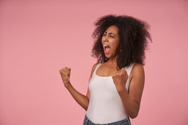 Mulher alegre, encaracolada de pele escura, camisa branca e jeans posando em rosa com os punhos levantados, olhando para o lado alegremente e gritando enquanto torce pelo time favorito