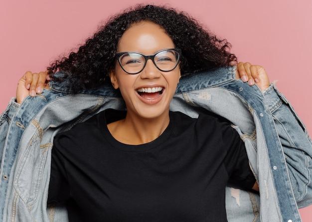 Mulher alegre encaracolada experimenta nova jaqueta jeans, usa óculos ópticos, sorri amplamente, tem humor perfeito
