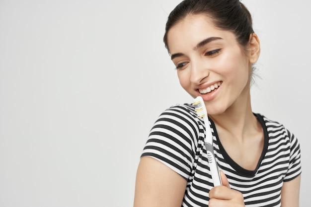 Mulher alegre escovando os dentes com uma escova de dentes de fundo claro