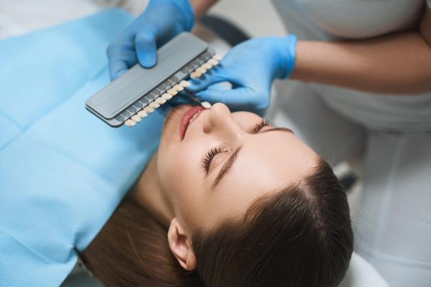 Mulher alegre está vindo ao médico para escolher folheados e melhorar seu sorriso com implantes