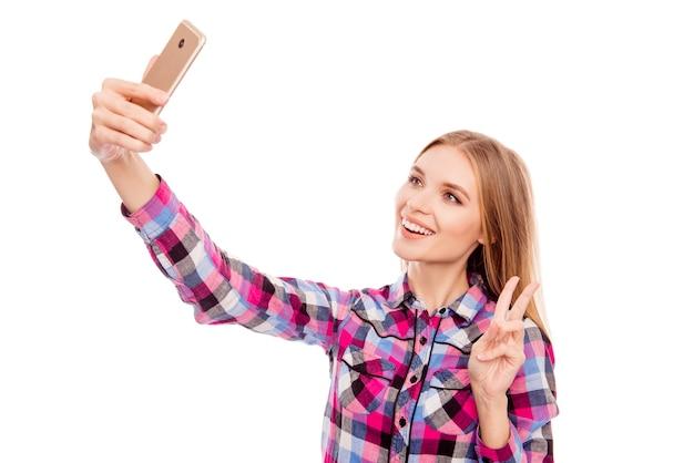 Mulher alegre fazendo foto com monopé e mostrando o sinal-v