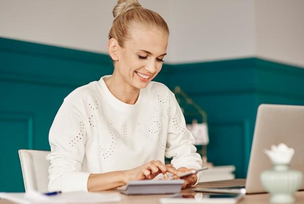 Mulher alegre fazendo orçamento em casa